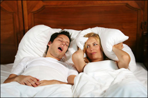 couple in bed, woman covering her ears while man is snoring